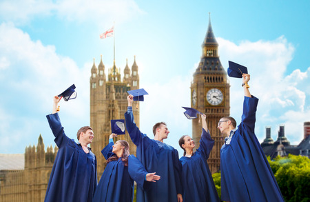education, graduation and people concept - group of smiling students in gowns waving mortarboards over london city and big ben clock tower background