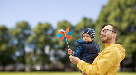 family, childhood, fatherhood, leisure and people concept - happy father and little son with pinwheel toy outdoors over summer park background