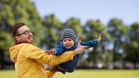 Familie, Kindheit, Vaterschaft, Freizeit und Menschen Konzept - glücklicher Vater und kleiner Sohn spielen und Spaß im Freien über Sommer Park Hintergrund Standard-Bild