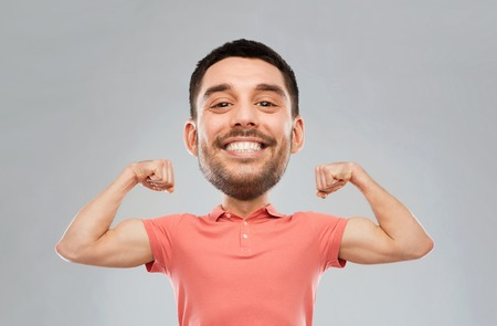 power, fitness, strength, sport and people concept - happy smiling young man showing biceps over gray background (funny cartoon style character with big head)