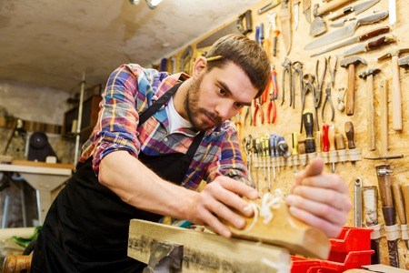 woodwork: profession, carpentry, woodwork and people concept - carpenter working with plane and wood plank at workshop