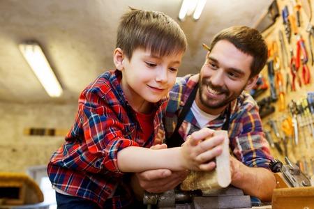 familia, carpintería, carpintería y concepto de la gente - padre e hijo pequeño se trabaja con tablones de madera en el taller