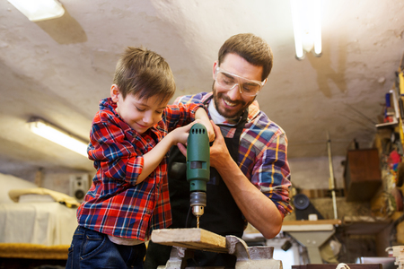 father and son: family, carpentry, woodwork and people concept - father and little son with drill perforating wood plank at workshop