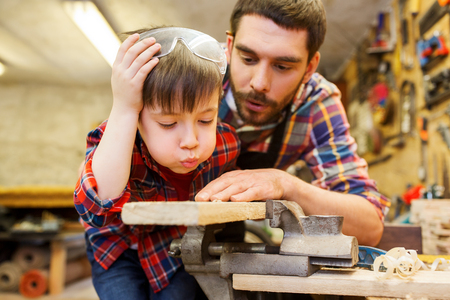 carpenter vise: family, carpentry, woodwork and people concept - father and little son working with wood plank at workshop