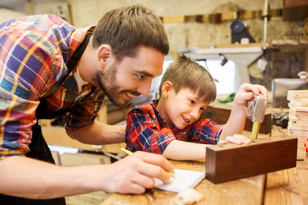 family, carpentry, woodwork and people concept - father and little son with ruler and pencil measuring wood plank and writing dimensions to notebook at workshop