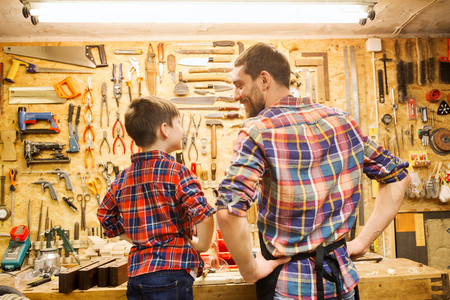 family, carpentry, woodwork and people concept - happy father and little son working with work tools and wood planks at workshop Stockfoto