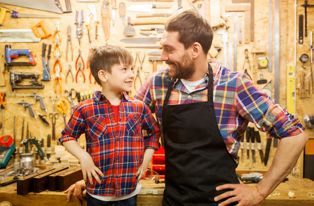 family, carpentry, woodwork and people concept - happy father and little son working with work tools and wood planks at workshop Imagens