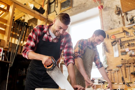 chippy: profession, carpentry, woodwork and people concept - carpenters working with saw and wood plank at workshop Stock Photo