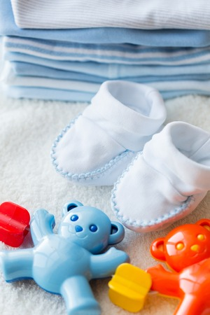 bootees: babyhood, childhood, toys, clothing and object concept - close up of baby rattle with bootees and clothes for newborn boy on towel Stock Photo