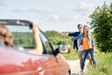 hitched: road trip, hitchhike, travel, gesture and people concept - happy couple hitchhiking and stopping car at countryside road Stock Photo