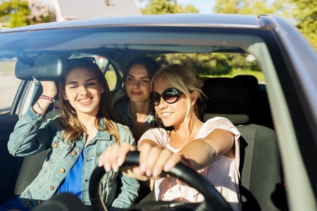 summer vacation, holidays, travel, road trip and people concept - happy teenage girls or young women driving in car Banco de Imagens