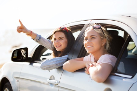 summer vacation, holidays, travel, road trip and people concept - happy teenage girls or young women sitting in car at seaside and pointing finger to something Banco de Imagens