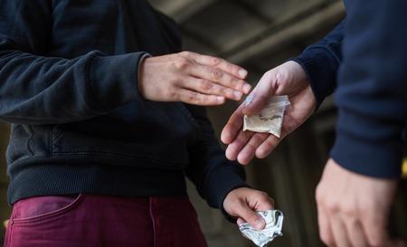 drug trafficking, crime, addiction and sale concept - close up of addict buying dose from drug dealer on street Standard-Bild