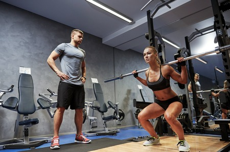 sport fitness: sport, fitness, bodybuilding, lifestyle and people concept - man and woman with bar flexing muscles in gym Stock Photo