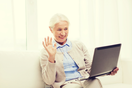 computer age: technology, age, gesture, communication and people concept - happy senior woman with laptop computer having video chat at home and waving hand