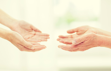 people, age, family, care and support concept - close up of senior woman and young woman reaching hands out to each other