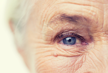 aging woman: age, vision and old people concept - close up of senior woman face and eye