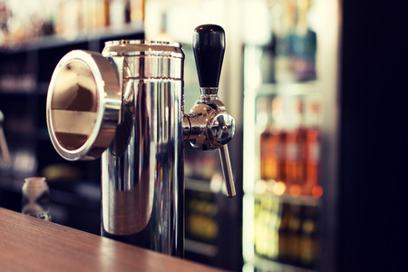 single beer: drink, equipment and object concept - close up of single tap chrome draft beer kegerator tower at bar or pub