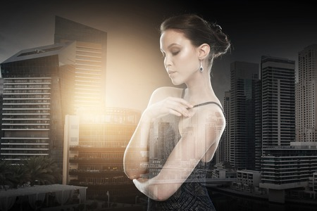 asian style: beauty, jewelry, wedding accessories, people and luxury concept - beautiful asian woman with diamond earring over dubai city with double exposure background Stock Photo