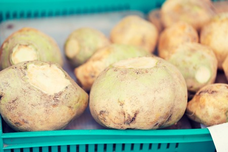 swede: sale, harvest, food, vegetables and agriculture concept - close up of swede or turnip in plastic box at street market