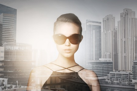 eyewear fashion: accessories, eyewear, fashion, people and luxury concept - beautiful young woman in elegant black sunglasses over dubai city with double exposure background Stock Photo