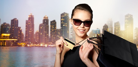 sale, finances, fashion, people and luxury concept - happy beautiful young woman in black sunglasses with credit card and shopping bags over night dubai city lights background