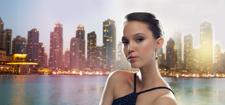 jewel: beauty, jewelry, people and luxury concept - beautiful young asian woman with earring over dubai city night lights background Stock Photo