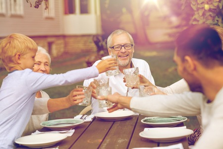 house family: family, happiness, generation, home and people concept - happy family having holiday dinner outdoors