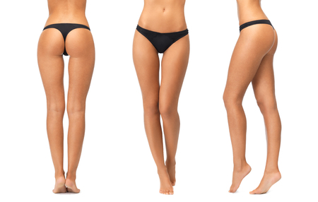 pies sexis: gente, belleza, cuidado del cuerpo, la ropa interior y el concepto de adelgazamiento - piernas femeninas y abajo en bragas negras sobre fondo blanco Foto de archivo