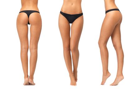 piedi nudi di bambine: persone, bellezza, cura del corpo, biancheria intima e il concetto di dimagrimento - gambe femminili e fondo in mutandine del bikini nero su sfondo bianco