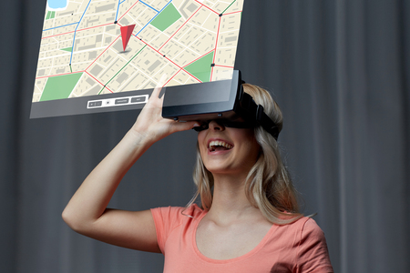 technology, virtual reality, cyberspace, entertainment and people concept - happy young woman with virtual reality headset or 3d glasses at home looking at gps navigator map projection Stock Photo