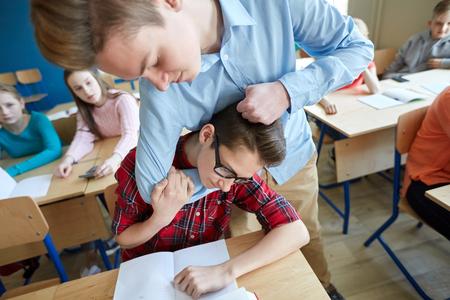 onderwijs, pesten, geweld, agressie en mensen concept - student jongen leed van klasgenoot spot