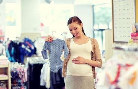 expectation: pregnancy, people, sale and expectation concept - happy pregnant woman shopping and buying baby bodysuit at children clothing store