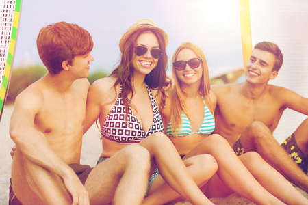 friendship, sea, summer vacation, water sport and people concept - group of smiling friends wearing swimwear and sunglasses with surfboards on beach