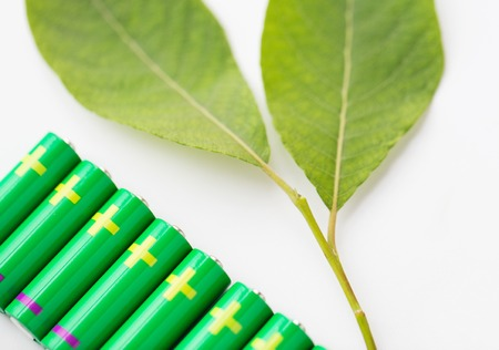 recycling, energy, power, environment and ecology concept - close up of green alkaline batteries and leaf Stock Photo