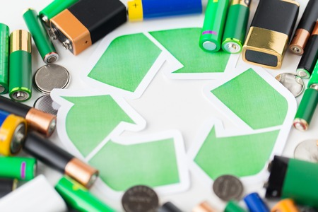 utilization: waste recycling, garbage disposal, environment and ecology concept - close up of used alkaline batteries and green recycling symbol