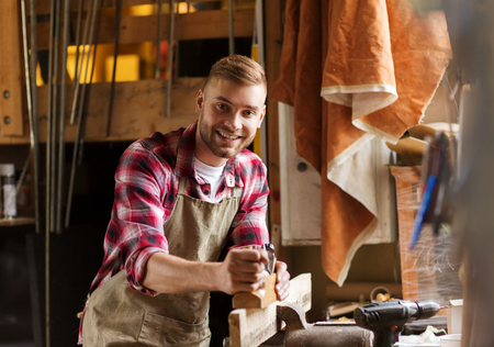profession, people, carpentry, woodwork and people concept - happy carpenter with jointer planing wood plank at workshop Stock Photo