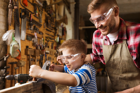 family, carpentry, woodwork and people concept - father and little son with plane working with wood plank at workshop Stock Photo