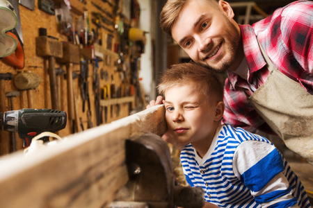 family, carpentry, woodwork and people concept - father and little son testing wood plank evenness at workshop