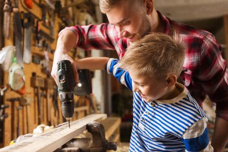 Rodina, tesařství, ze dřeva a lidé koncept - otec a malý syn s vrtací perforování dřevěného prkna v dílně Reklamní fotografie