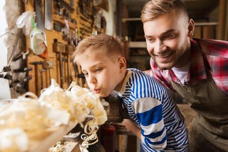 Familie, Zimmerer, Holz und Menschen Konzept - Vater und Sohn Späne aus Holz Brett an der Werkstatt weht