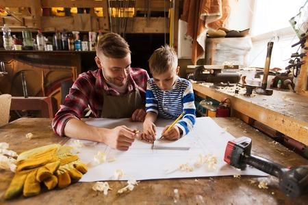 familie, timmerwerk, houtwerk en mensen concept - gelukkige vader en zoontje met blauwdruk op workshop