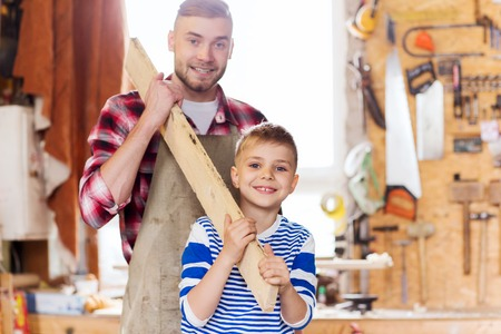 work together: family, carpentry, woodwork and people concept - happy father and little son carrying wood plank at workshop