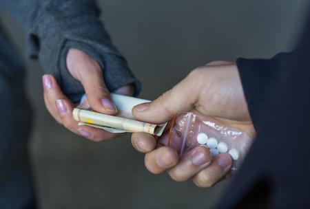 le trafic de drogue, la criminalité, la toxicomanie et la vente concept - gros plan de toxicomane avec la dose d'achat de l'argent des dealers dans la rue