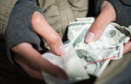 junky: drug trafficking, crime, addiction and sale concept - close up of addict hands with drugs and money