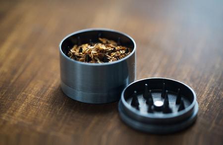 molinillo: el uso de drogas, abuso de sustancias, la adicción y el fumar concepto - cerca de la marihuana o el tabaco y el molinillo de hierba