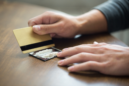 drug use: drug use, people, addiction and substance abuse concept - close up of addict hands with crack cocaine drug dose track on mirror and credit card