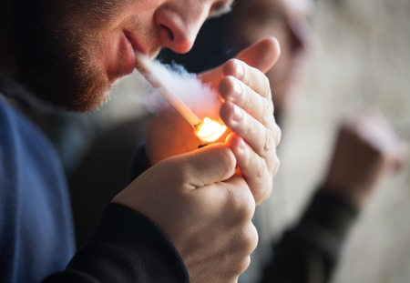street drug: smoking, substance abuse, addiction and bad habits concept - close up of young people lighting cigarette outdoors Stock Photo