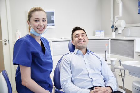 health care and medicine: people, medicine, stomatology and health care concept - happy female dentist with man patient at dental clinic office