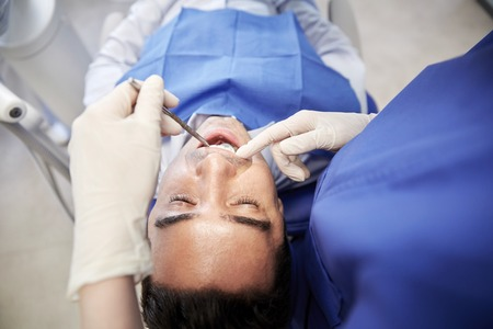 stomatological: people, medicine, stomatology and health care concept - close up of female dentist with dental mirror checking up male patient teeth at dental clinic office Stock Photo